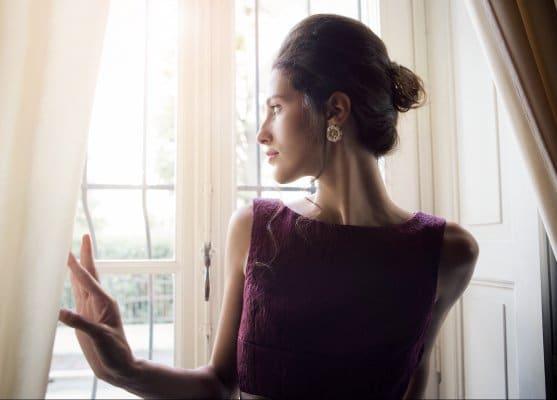 Model mit Etuikleid am Fenster